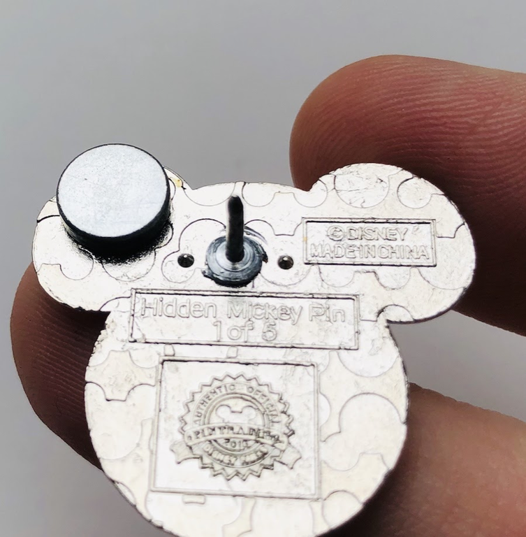 A magnet sticking to the back of a fake Disney pin